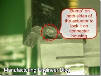 Right angle connector with bump show on both actuator sides of connector to lock it on the housing.